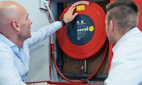 Twee medewerkers van Hydroscope controleren een brandslanghaspel