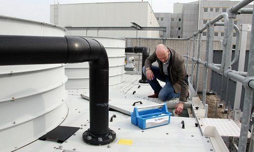 Medewerker neemt een watermonster van een koeltoren.
