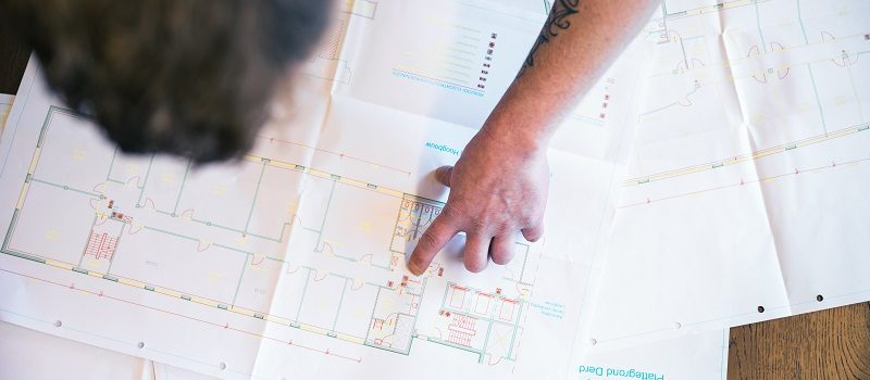 Medewerker beoordeelt een tekening van een drinkwaterinstallatie.