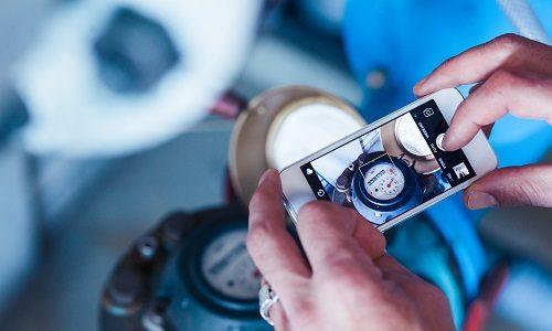 Medewerker maakt een foto van een watermeter dit helpt bij duurzaam watergebruik