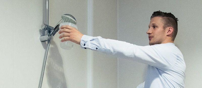 Medewerker neemt een watermonster van een douche